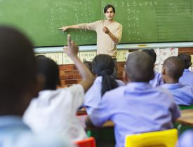 Teacher pointing to math problem on the blackboard