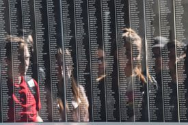 People looking at a memorial wall naming the victims of the Holocaust.
