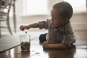Young boy laying on his stomach on the floor placing coins in a glass jar