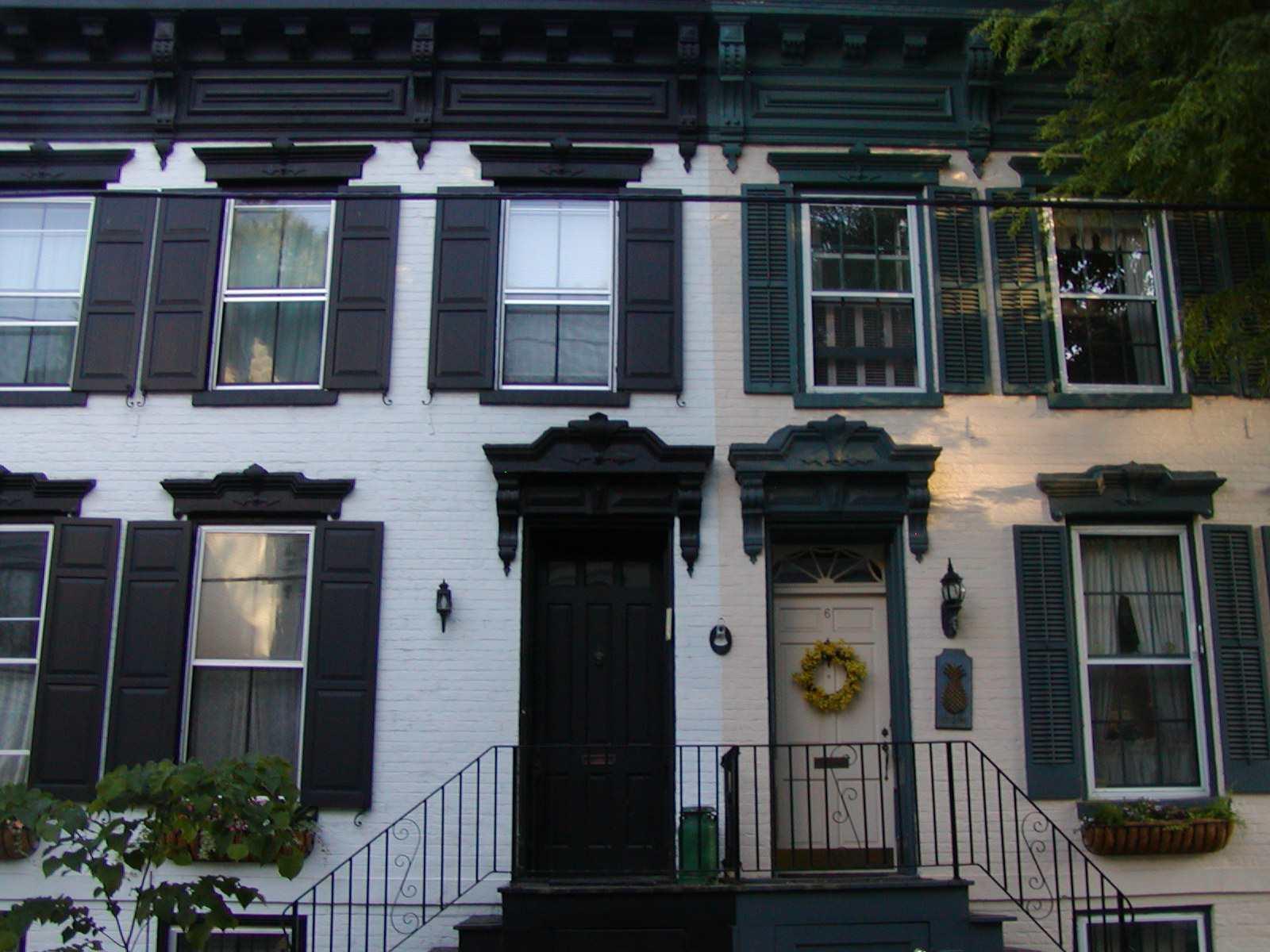 Casa adosada dividida solo por colores de pintura, ladrillos blancos y crema