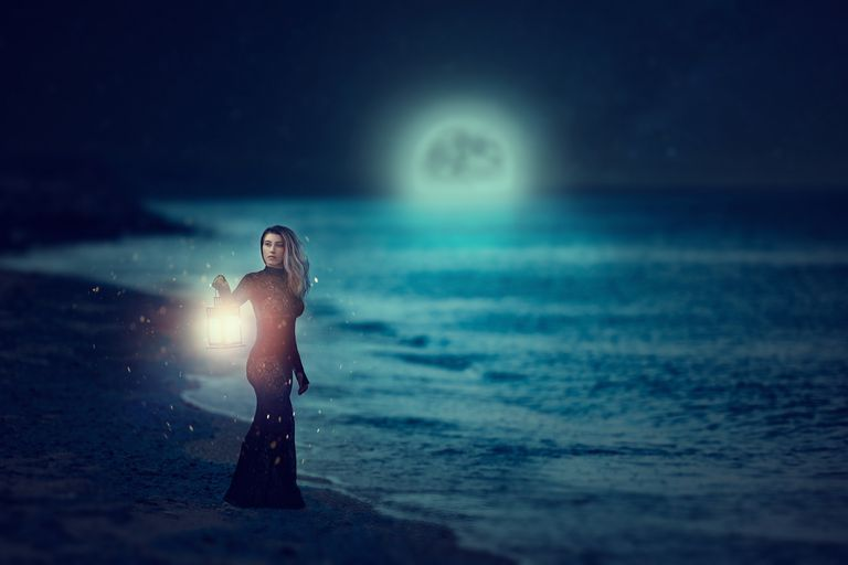 Woman walking on the beach during the full moon