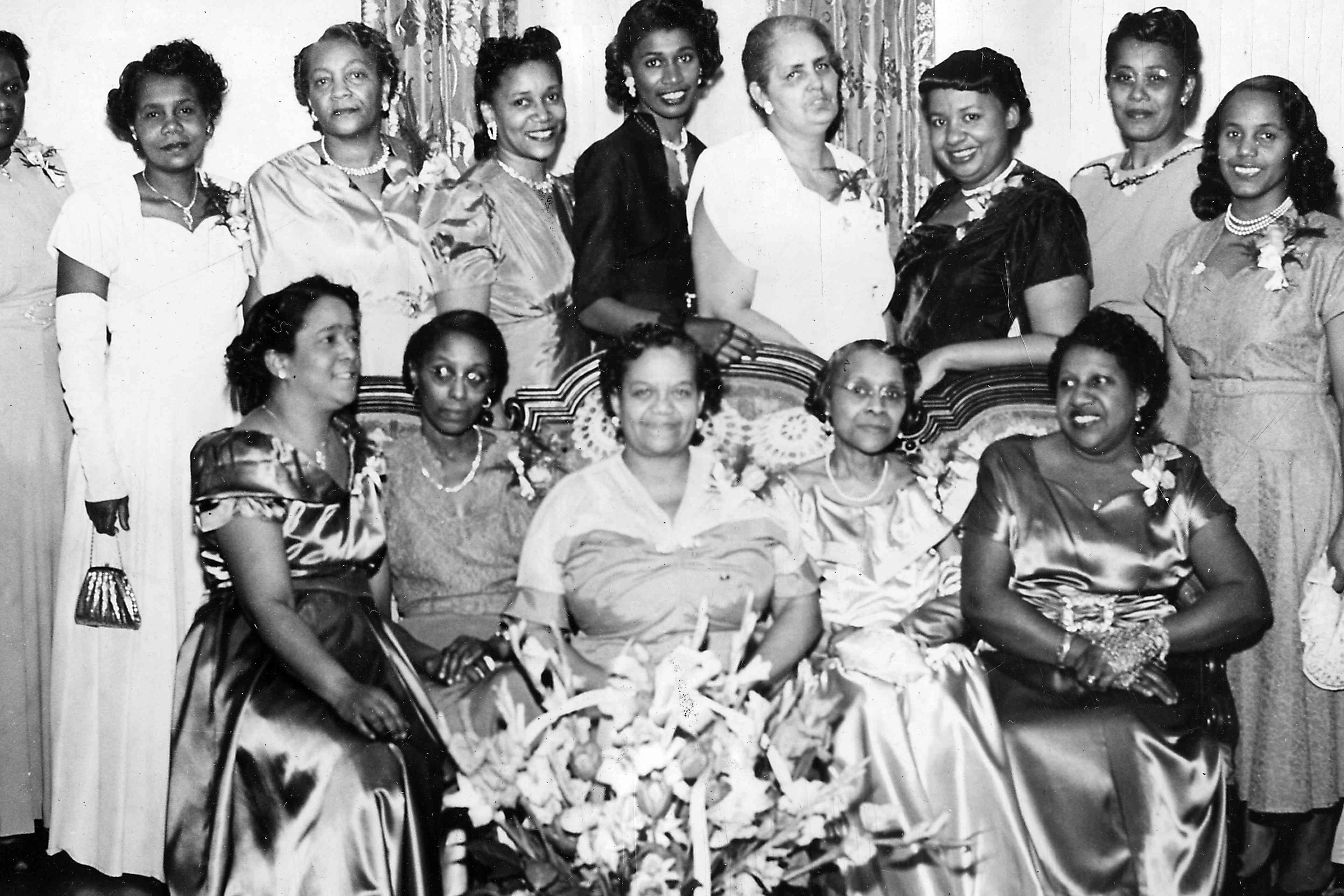 Zeta Phi Beta sorority members standing and founders sitting on a couch