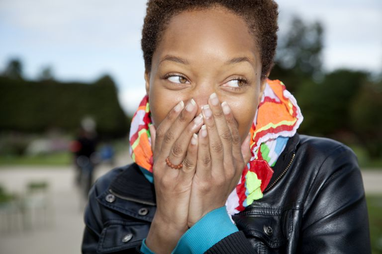 Woman laughing, hands cover mouth
