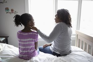 mom talking to daughter on bed