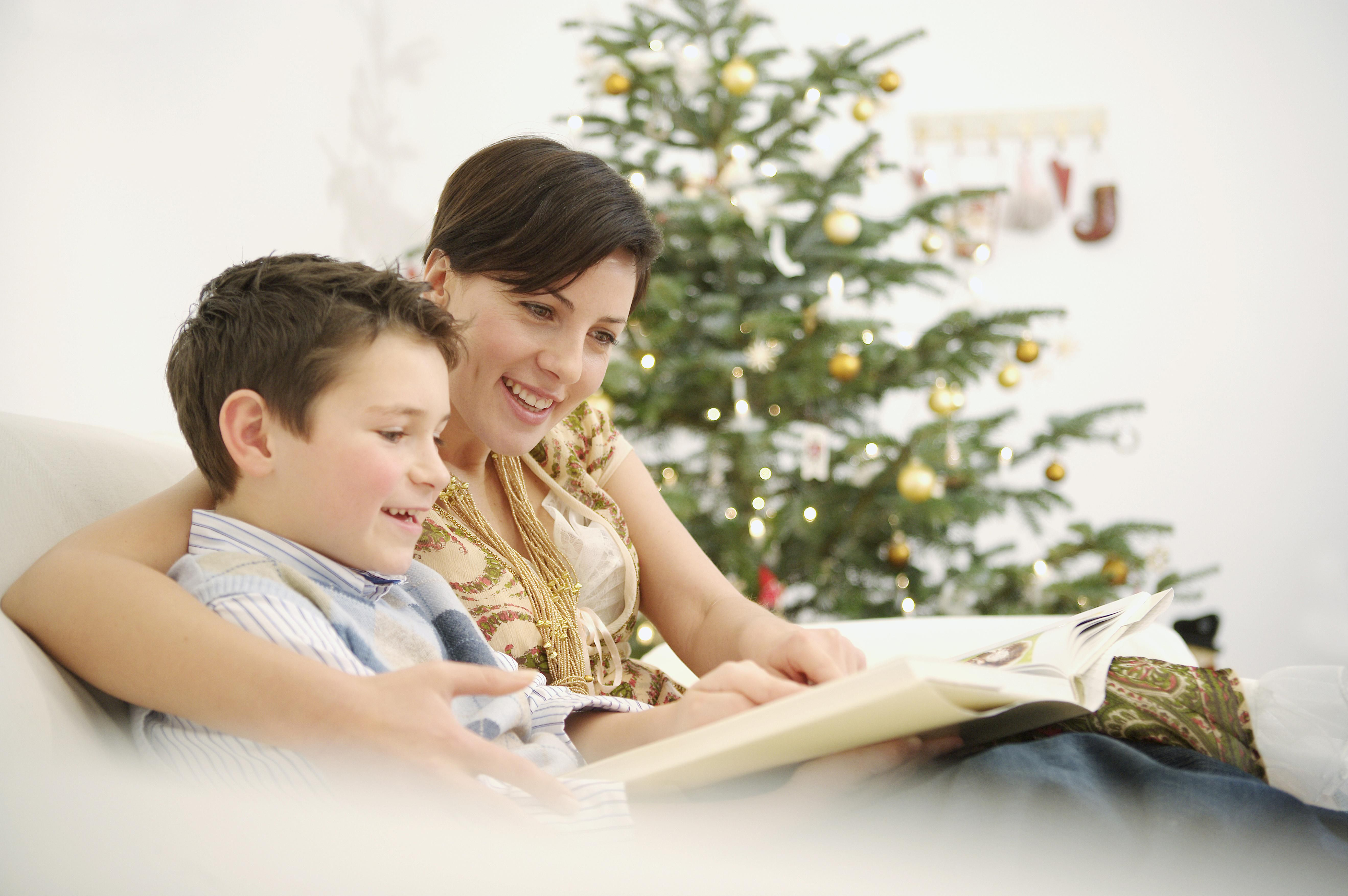Mother and young son reading on sofa at Christmastime