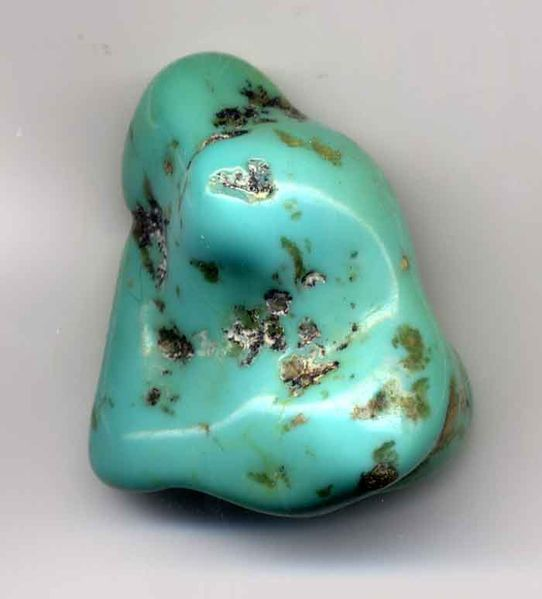 Turquoise pebble that has been smoothed by tumbling.
