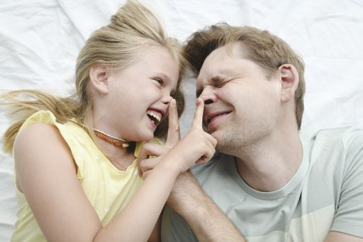 Father happy smiling daughter in bed - stock photo
