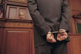 Businessman in handcuffs faces judge in court