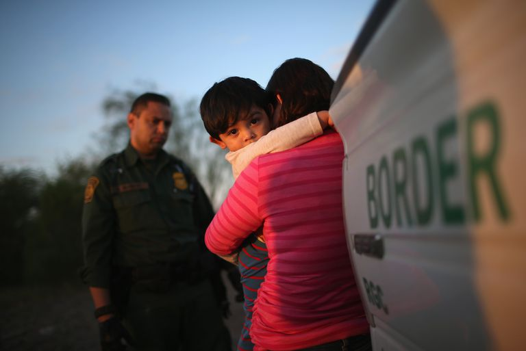 child and mom hugging in front of border security