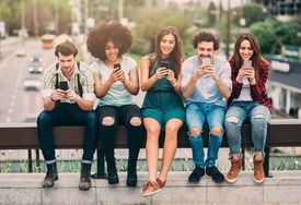Several young people sitting on a bridge railing using their smartphones on a sunny day.