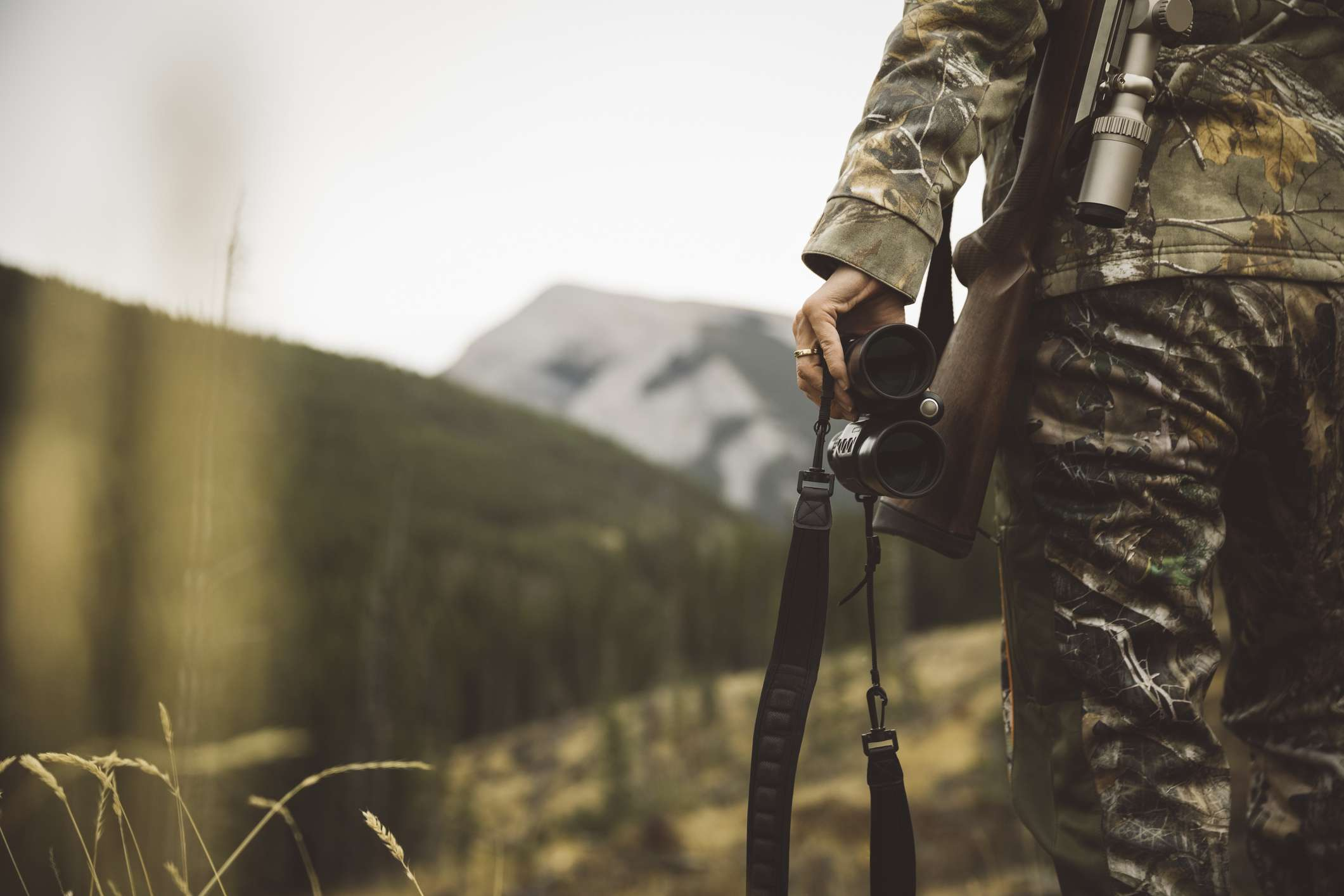 Female hunter in camouflage carrying binoculars and hunting rifle in field