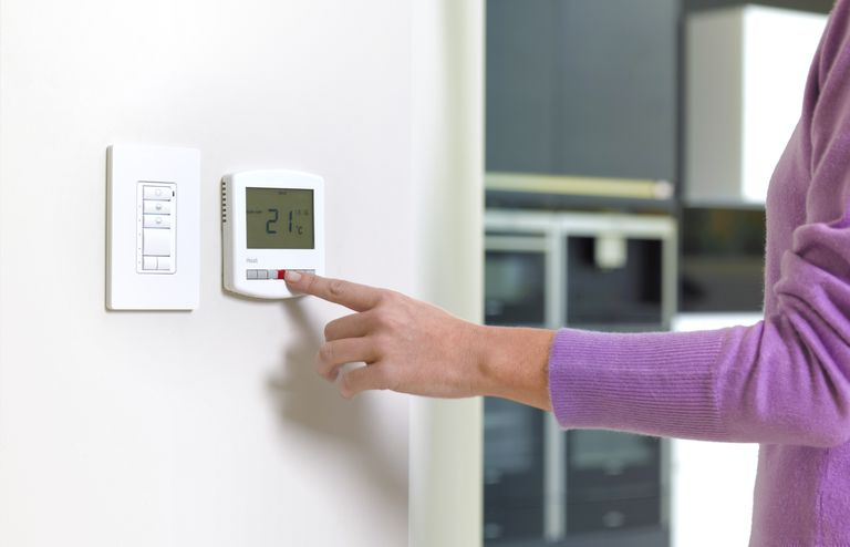 A woman adjusting a thermostat