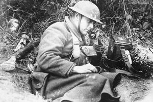 Soldier in foxhole holding radiotelephone receiver