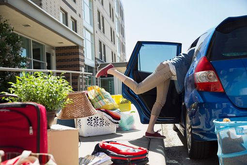 College student reaching in car moving into dorm