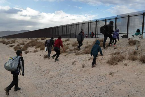 Migrants approaching the U.S. border fence.