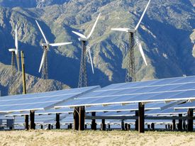 A series of solar panels on the ground, with four modern windmills behind them. In the background is a mountain range.