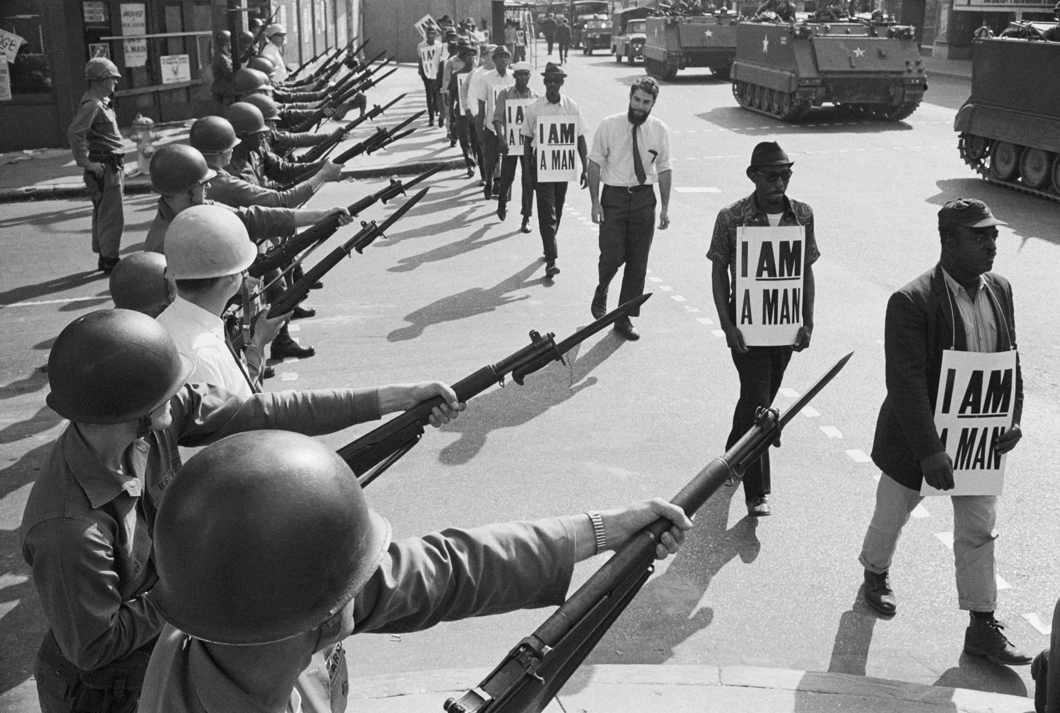 U.S. National Guard troops block off Beale Street as Civil Rights marchers wearing placards reading,