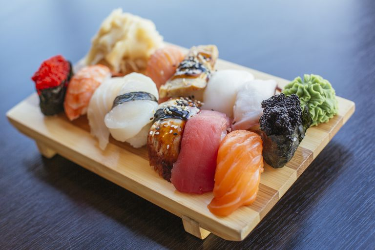 A variety of nigiri sushi on a bamboo serving board