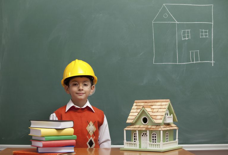 Male child engineer in hard hat designing a new house, model house on desk, drawing on chalkboard