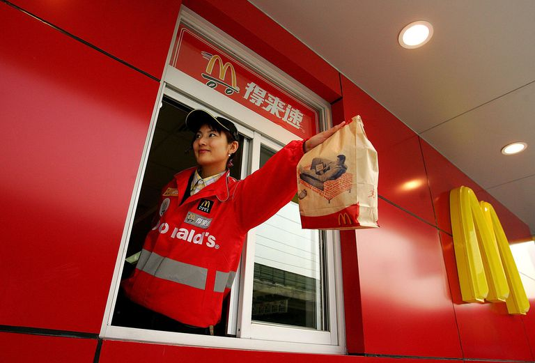 A Chinese woman serving food at a McDonald's drive-thru in Beijing is a classic example of George Ritzer concept of the McDonaldization of society.