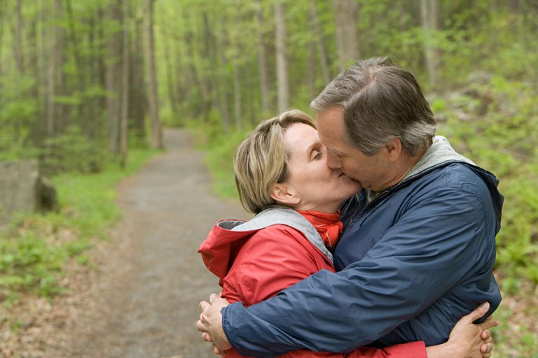 Older couple kissing by a wooded path