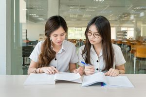 Two girls talking about class work