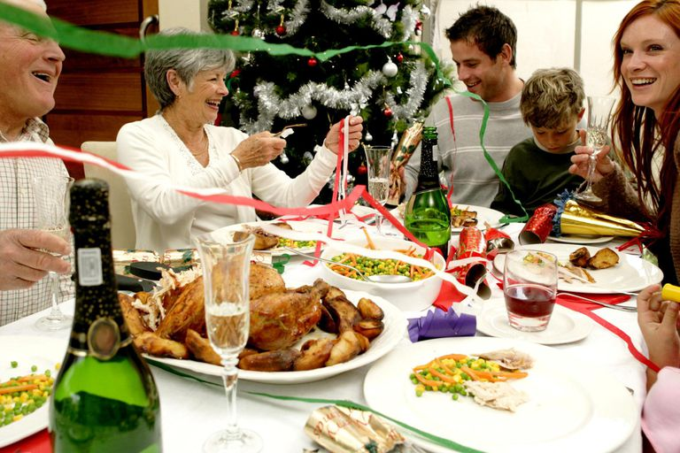 Streamers falling on family at table having Christmas dinner, smiling