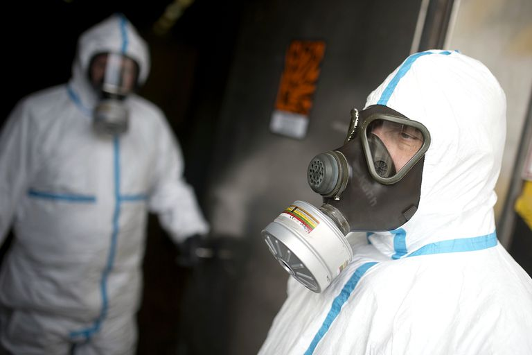 Two figures in hazmat suits with gas masks enter a bunker doorway