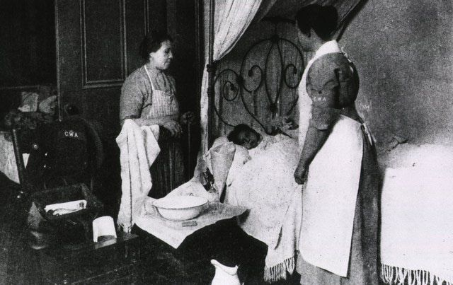 A picture of a child with influenza in bed, with her mother and a visiting nurse standing nearby.