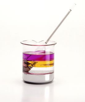 A beaker containing fluid with layers of different colors. The top layer is purple, the next layer is amber, then clear, then a whitish liquid. A hydrometer is sticking out of the beaker.