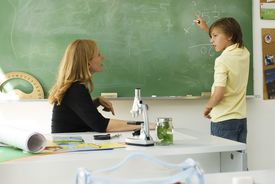 Boy solving math problem on blackboard, looking at teacher for assistance