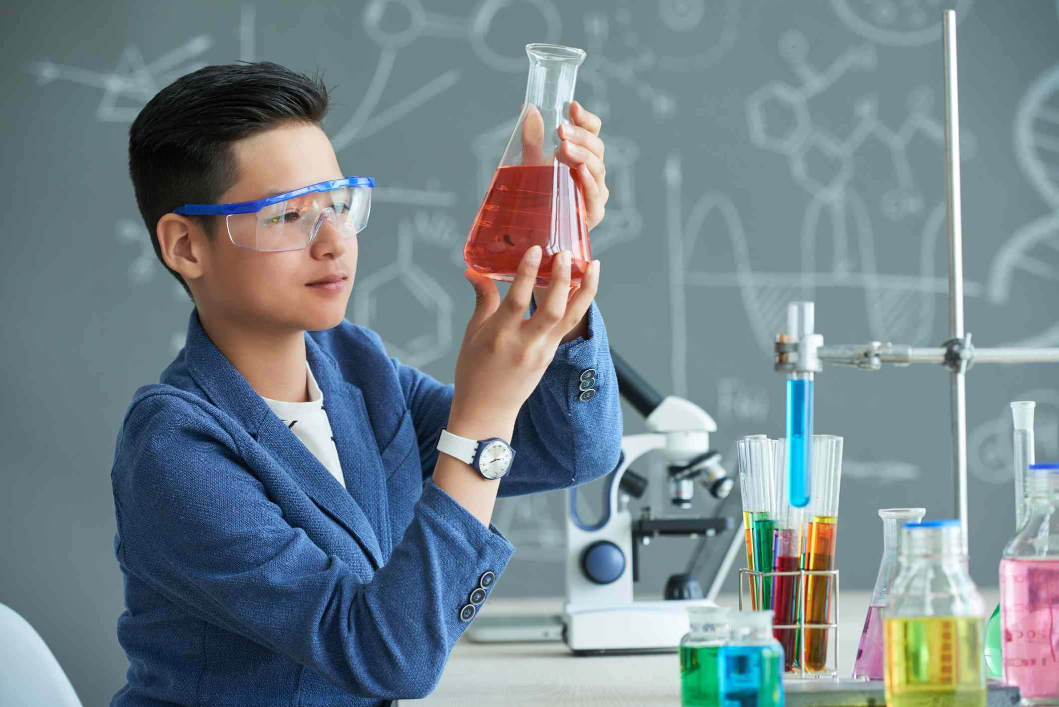 School boy looking at flask with red liquid