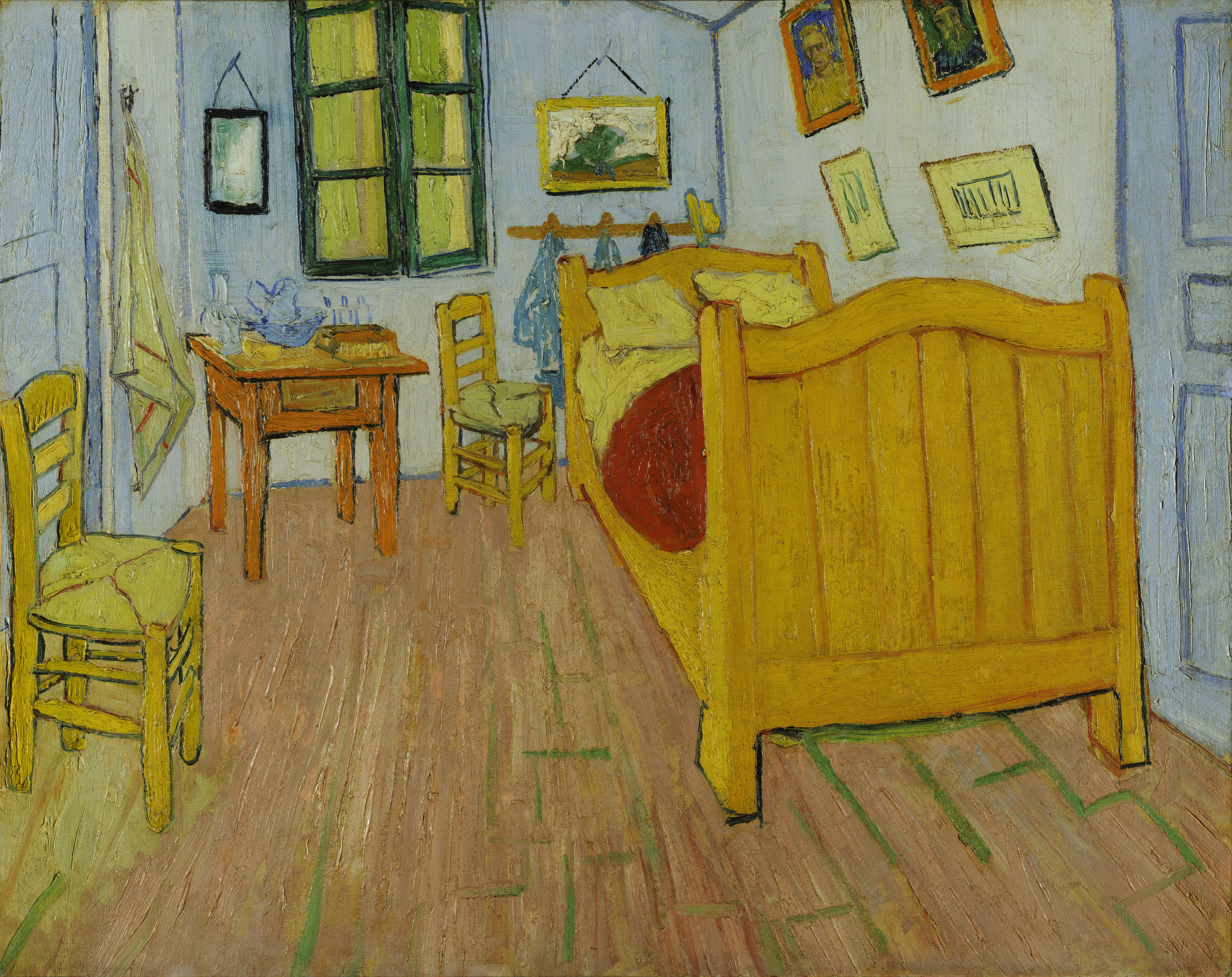 Small bedroom with blue walls, yellow bed, two wicker chairs and a small table.
