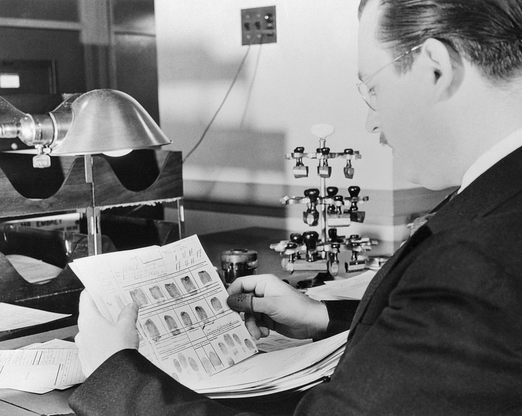 FBI criminologist examines fingerprints.