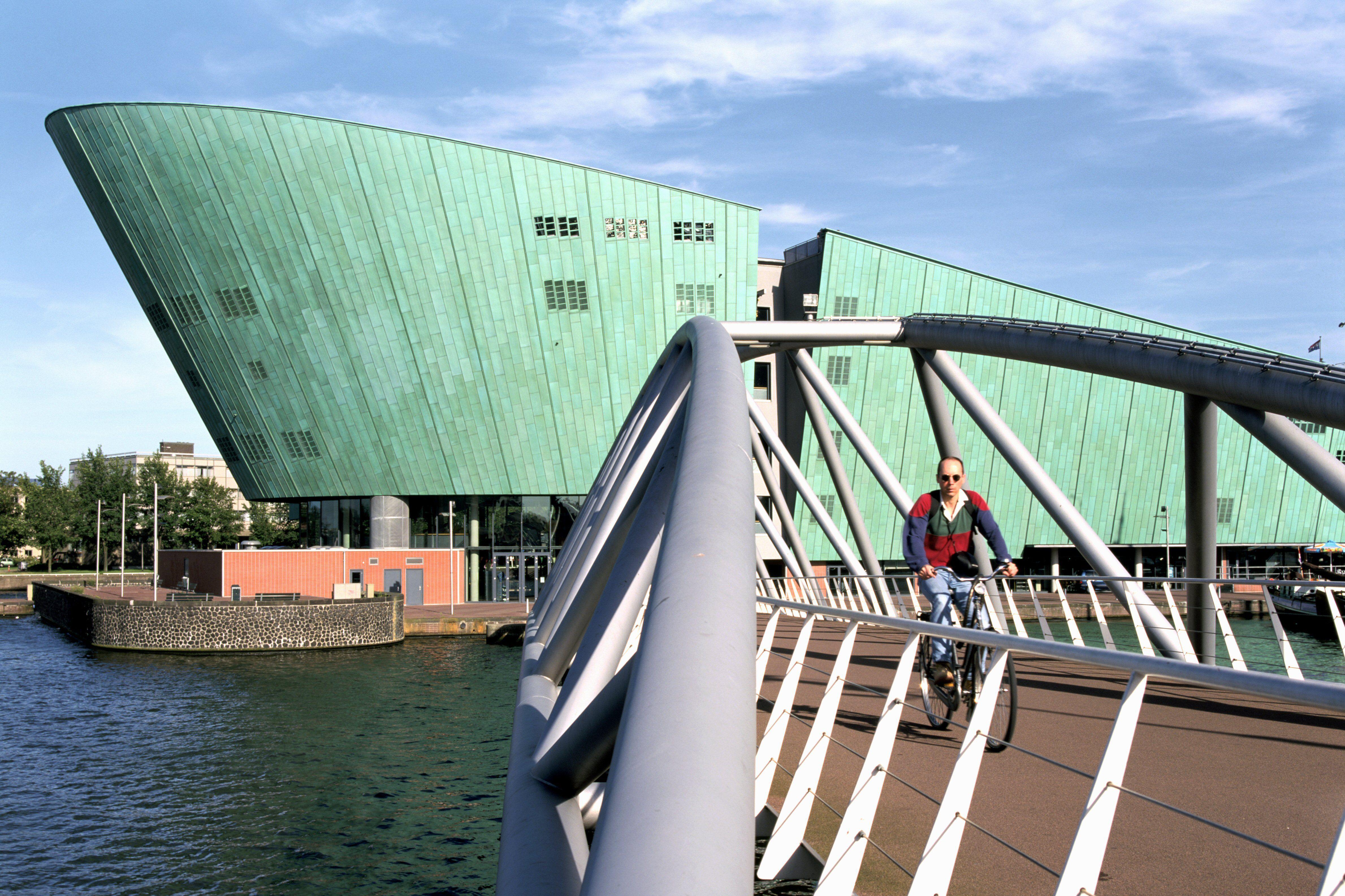 man on bicycle cross small bridge to asymmetrical blob-like green ship-like structure