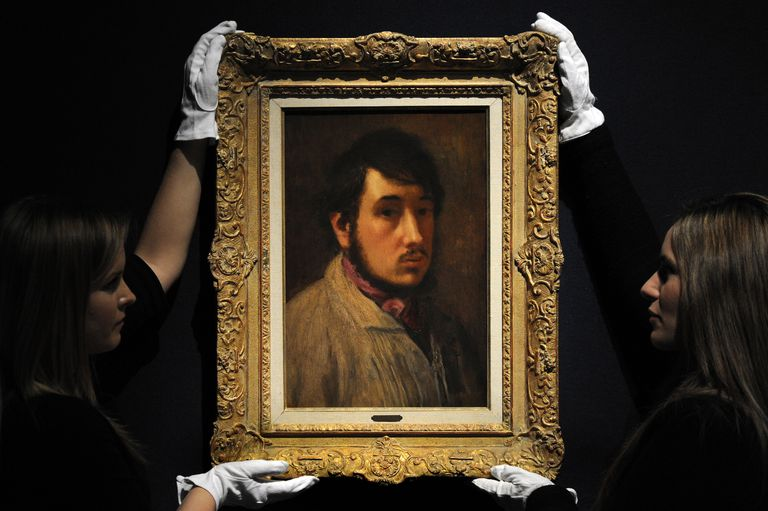 "Employees pose with a painting by French artist Edgar Degas entitled ""Autoportrait""."