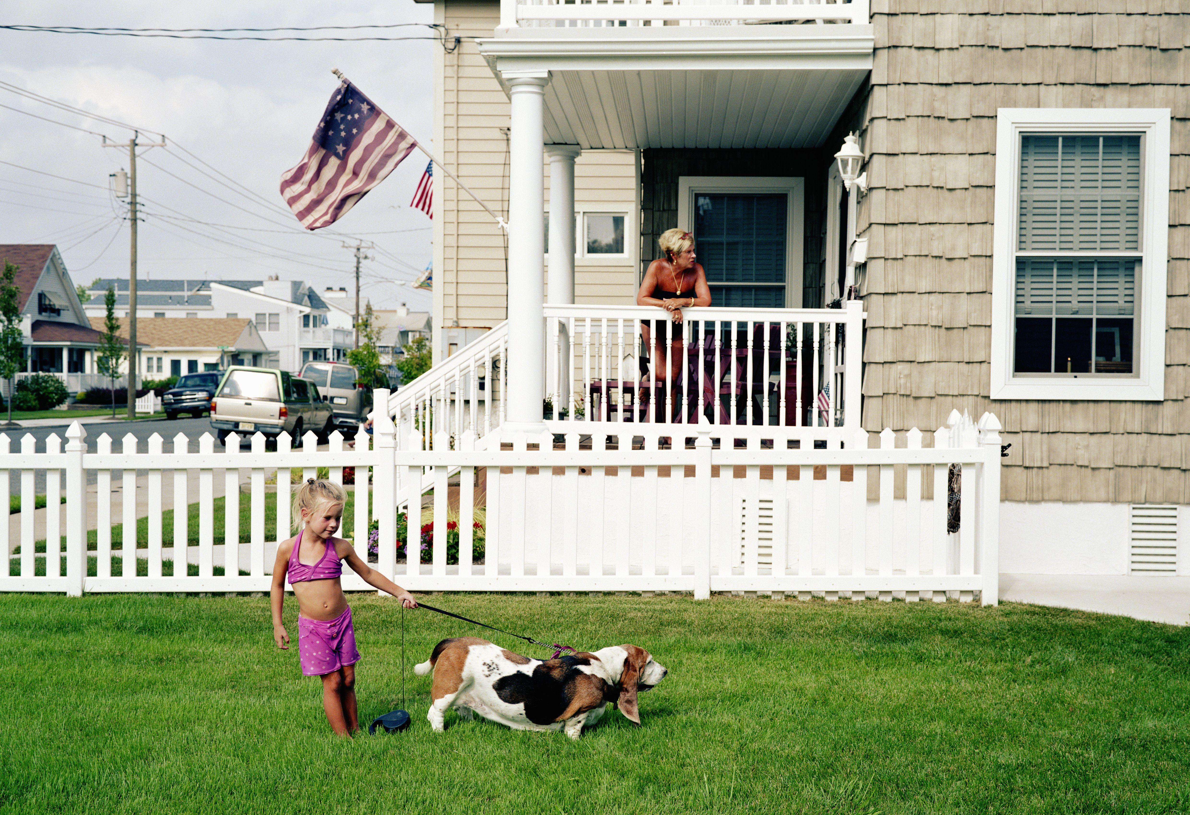 Niña con perro delante de su casa. Bandera americana ondeando