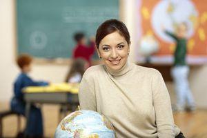 School administrator sitting next to a globe.