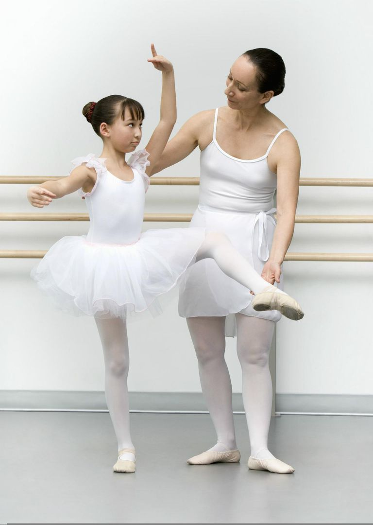 Teacher helping girl (10-12) in ballet class