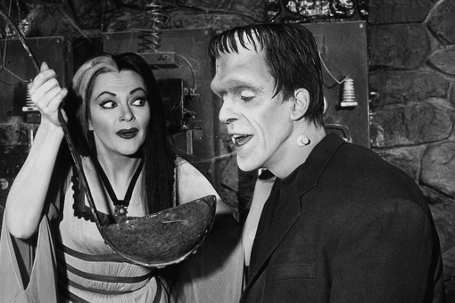 Fred Gwynne in the role of Herman Munster, alongside his costar Yvonne de Carlo