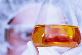 scientist looking at solution in beaker