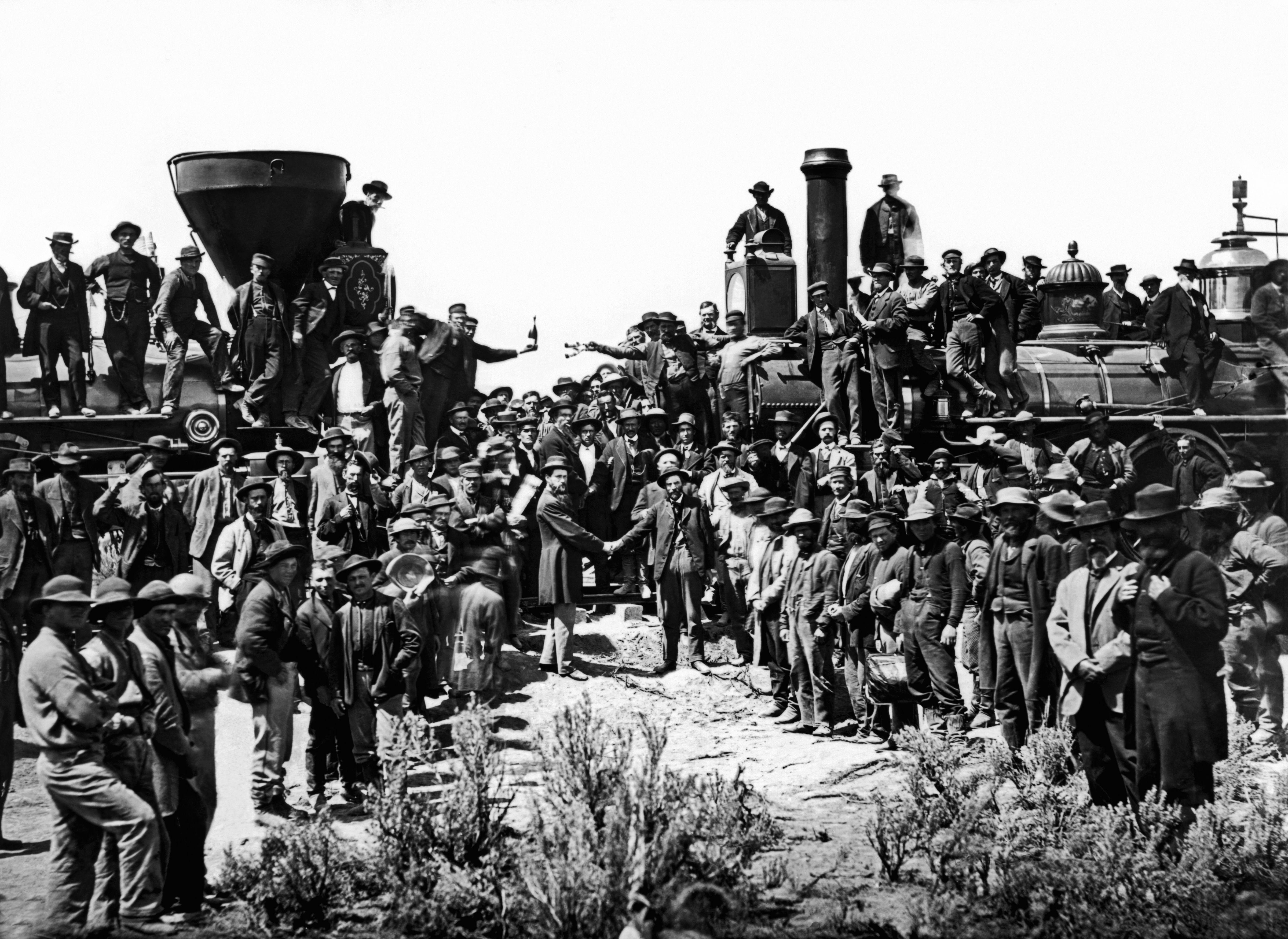 Crowd gathered around two locomotives.