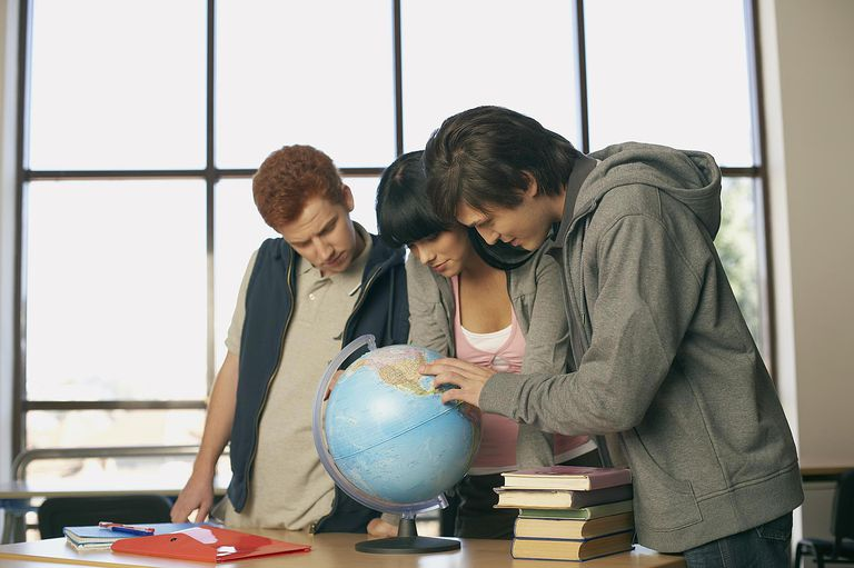 Teenagers looking at a globe