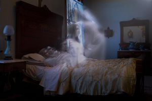 picture of a ghost rising from a dead body in a bed