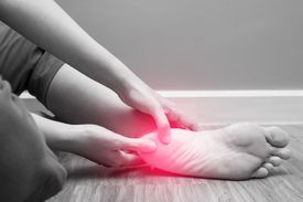 Female foot heel pain with red spot.