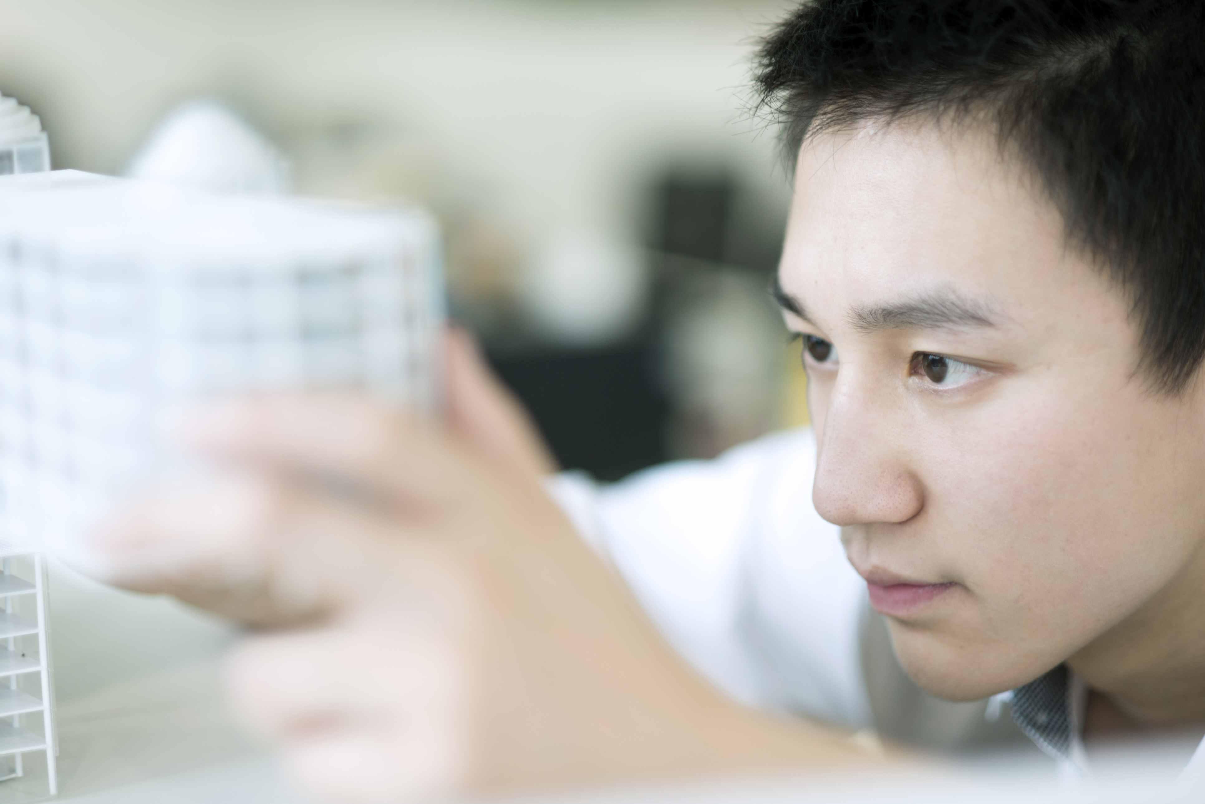 Asian student examining model