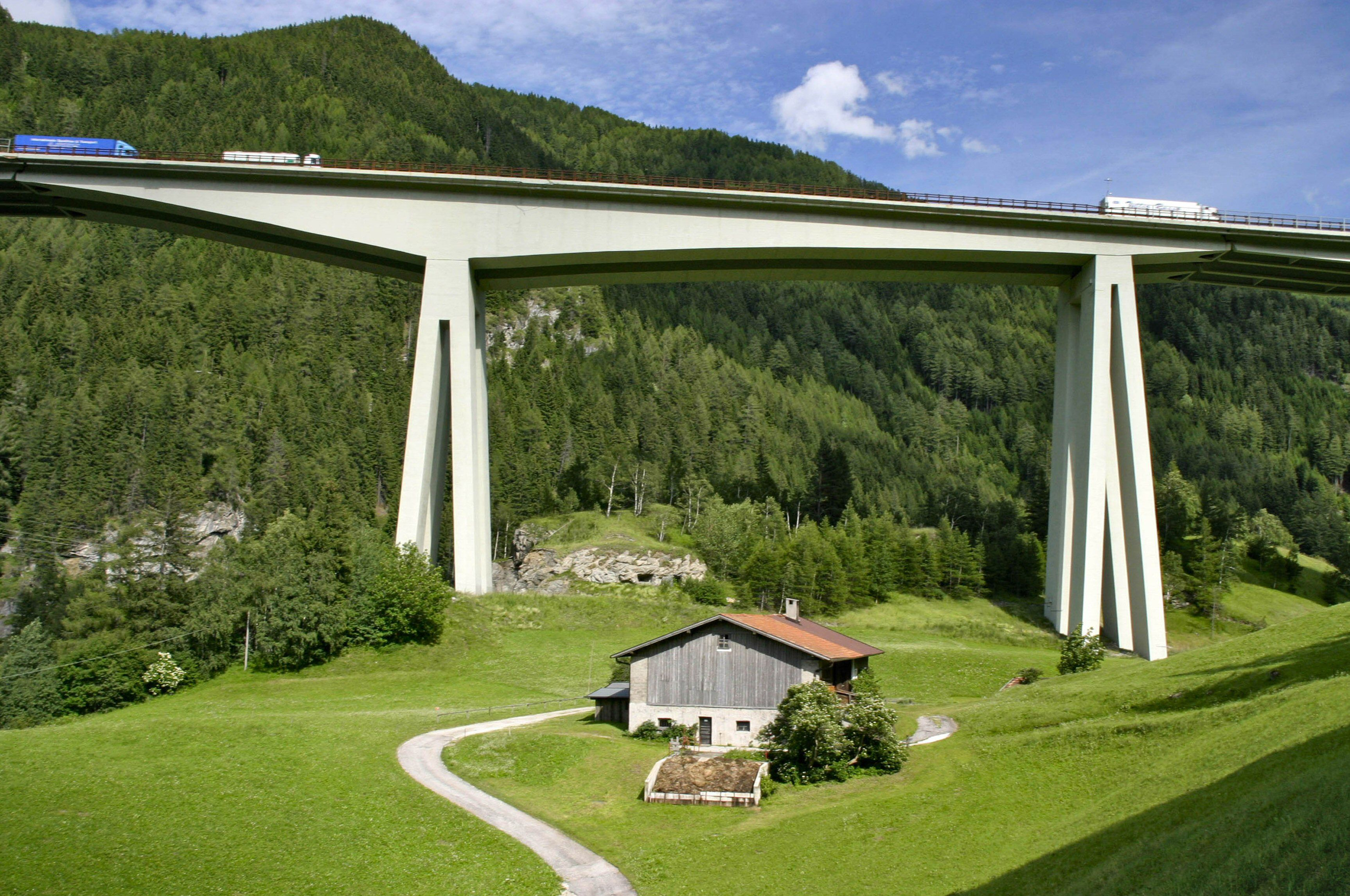 concrete bridge elevated above the mountains, valleys, and Alpine homes of Europe