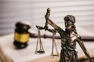 Close Up Of Lady Justice Against Gavel On Book