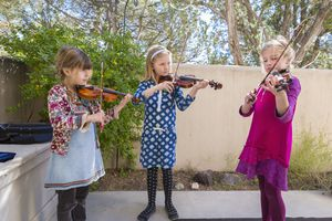 Music and learning - three girls playing violin outside