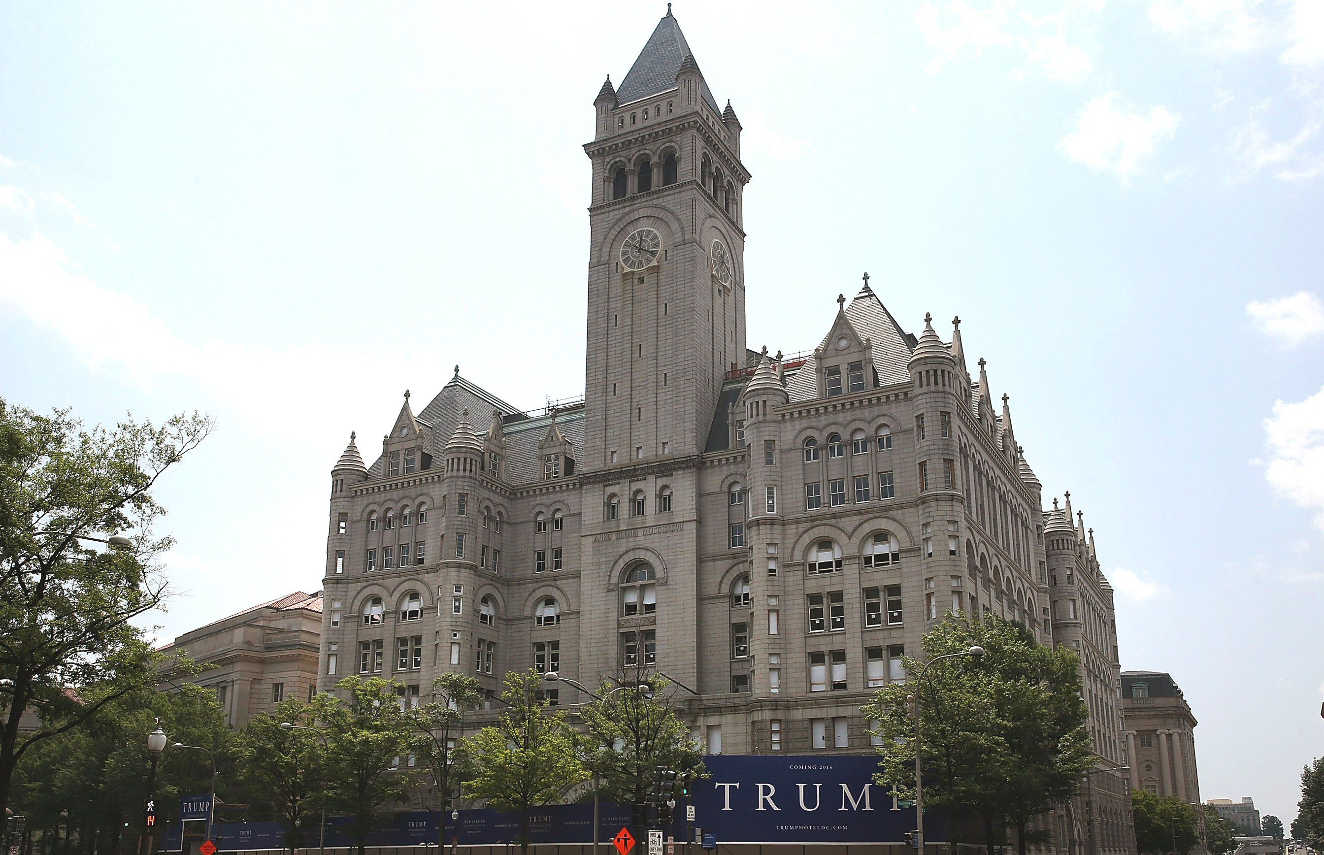 Photograph of the Old Post Office tower in Washington, District of Columbia, with TRUMP sign in front